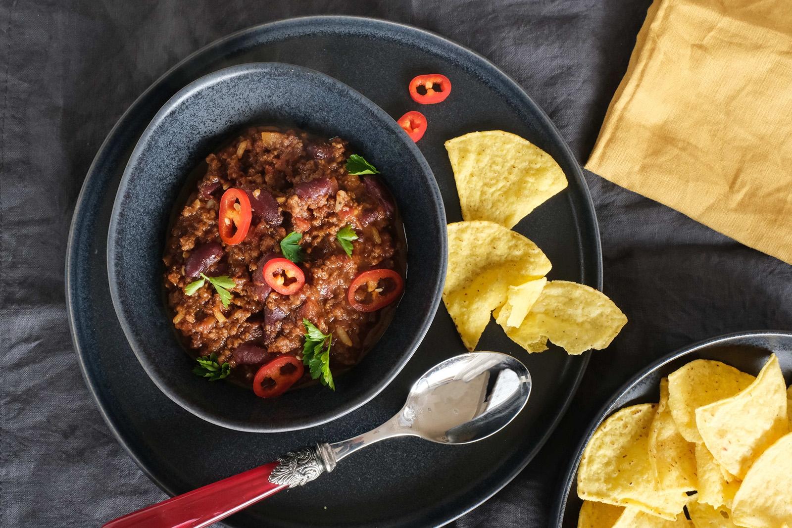 Mexické zahřívací pikantní jídlo s hovězím masem - to je chilli con carne. Servírujte s lupínky doritos
