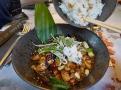Kuřecí Kung Pao s arašídy a jarní cibulkou. Servírují se z hráškovými lístky